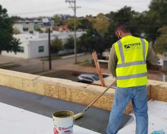 Roofer installing parapet flashing on commercial roofing project.