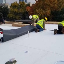 Our roofers laying down TPO single ply membrane over insulation for a new commercial flat roof project in Downtown OKC